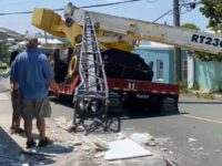 Tractor Trailer Carrying A Crane Tipped Over, Two Belco Poles Down, Building Damaged